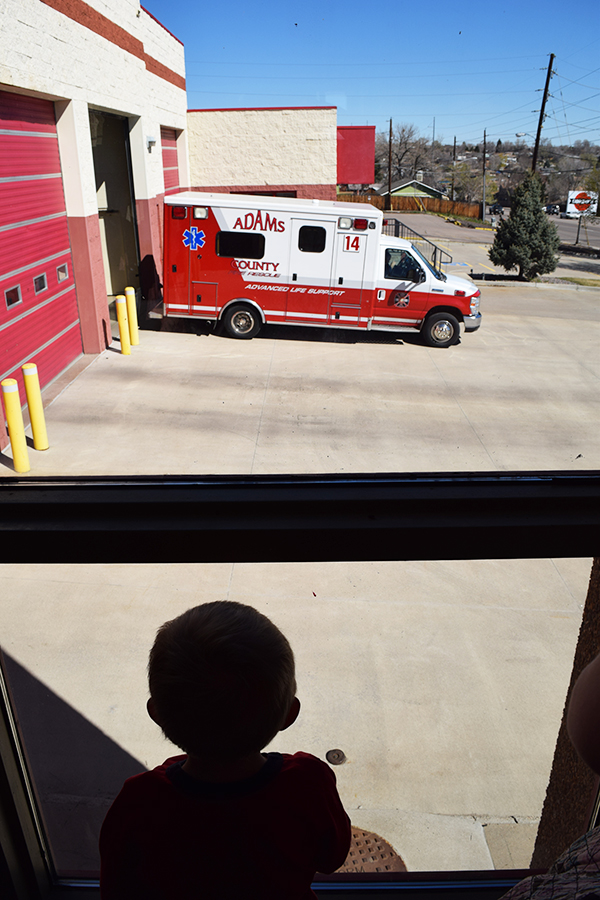 Ambulance leaving fire station while child watches